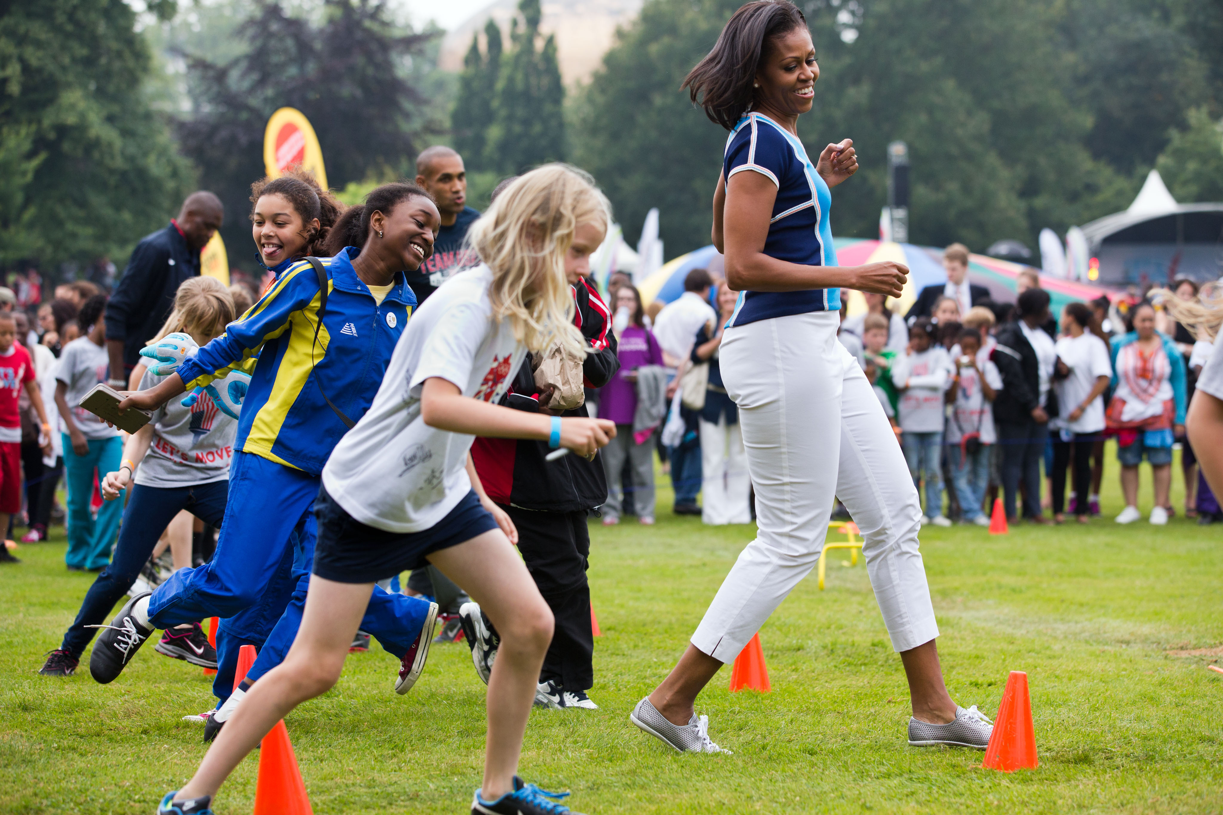 7b3cc03f25c9 ... First Lady Michelle Obama runs at an activity station during a ...