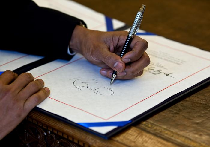 President Barack Obama signs a bill in the Oval Office, April 7, 2010.