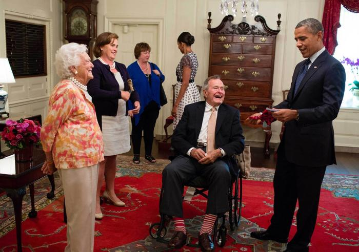 Former President George H. W. Bush and former First Lady Barbara Bush present President Barack Obama with a pair of socks in the Map Room of the White House, July 15, 2013.